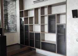 Встроенный стеллаж из ЛДСП вдоль стены. . Фасады: тонированное стекло серого цвета.