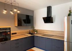 Фасады кухни: нижние - МДФ в матовой пленке; верхние - чёрное стекло в тонкой алюминиевой рамке.