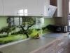 Выбраны природные мотивы в дизайне: фасады с древесной текстурой, стеклянный кухонный фартук с изображением природы, придающий индивидуальность гарнитуру. Фасады выполнены из пластика (Германия).