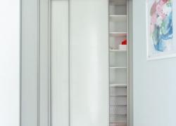 Приоткрытый шкаф купе. Много полочек для хранения вещей